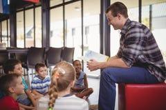 Schoolkids счастливого учителя уча в библиотеке Стоковое Фото