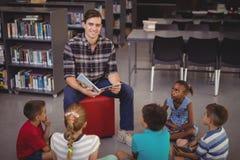 Schoolkids счастливого учителя уча в библиотеке Стоковое фото RF