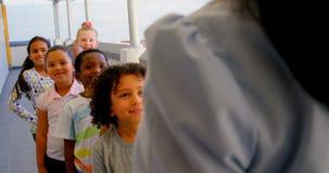 Schoolkids с учителем стоя в строке в прихожей в школе 4k акции видеоматериалы