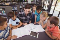 Schoolkids учителя уча в библиотеке Стоковое Изображение RF