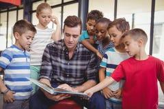 Schoolkids учителя уча в библиотеке Стоковые Изображения RF