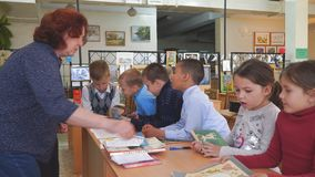 Schoolkids with books stand next to the teacher`s desk. Chapaevsk, Samara region, Russia - May 10, 2019: Elementary school of the city of Chapaevsk. Schoolkids stock footage
