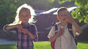 Schoolkids a boy and girl with backpacks blow a lot of soap bubbles during a recess in backlight in the open air. Schoolkids a boy and a girl with backpacks blow stock video footage