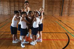 Schoolkids and female coach forming hand stack and looking at camera royalty free stock image