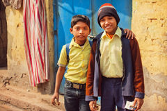 Schoolkids hugging on poor houses street of indian city. KOLKATA, INDIA - JAN 10: Unidentified schoolkids hugging on poor houses street of indian city on January Royalty Free Stock Photography