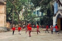 Schoolkids jumping with frisbee in green courtyard of school Stock Image