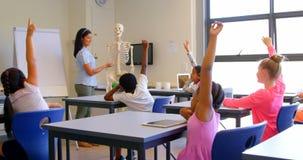 Schoolkids podnosi r?k? podczas gdy siedz?cy przy biurkiem w szkole podstawowej 4k zbiory