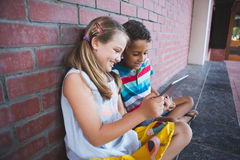 Schoolkids sitting in corridor and using digital tablets. At school Royalty Free Stock Photography