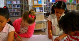 Schoolkids studiuje wpólnie przy stołem w szkolnej bibliotece 4k zbiory wideo
