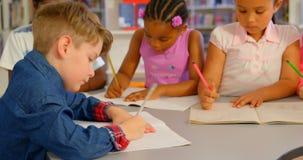 Schoolkids studiuje wp?lnie przy sto?em w szkolnej bibliotece 4k zbiory wideo