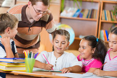 Schoolkids and their teacher at lesson Royalty Free Stock Photo
