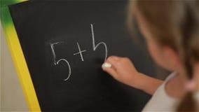 Schoolkind die eenvoudige wiskunde op schoolbord uitoefenen stock footage
