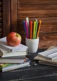 Schoolkind en studentenstudiestoebehoren Boeken, notitieboekjes, blocnotes, kleurpotloden, pennen, heersers en een verse rode app Royalty-vrije Stock Afbeelding