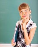 Schoolkind in klaslokaal dichtbij bord. royalty-vrije stock afbeelding
