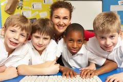 Schoolkinderen in de Klasse die van IT Computers met behulp van Stock Foto