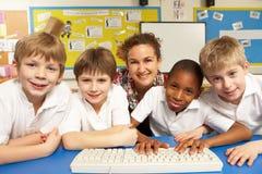 Schoolkinderen in de Klasse die van IT Computers met behulp van Stock Fotografie
