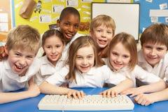 Schoolkinderen in de Klasse die van IT Computers met behulp van Stock Foto's