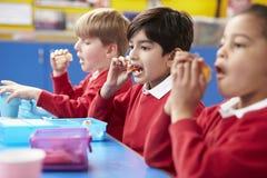 Schoolkinderen die bij Lijst zitten die Ingepakte Lunch eten Stock Foto's