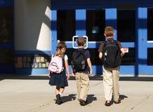 schoolkinderen die binnen gaan Stock Afbeeldingen