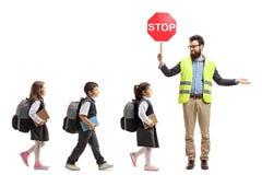 Schoolkinderen die in een lijn en een leraar met een veiligheid lopen ves stock afbeelding
