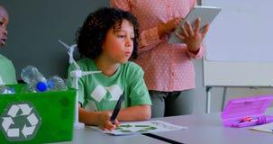 Schoolkinderen die over groene energie bestuderen en kringloop op bureau in klaslokaal 4k stock videobeelden