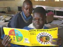 Schoolkinderen die sociaal studiesboek lezen stock foto's