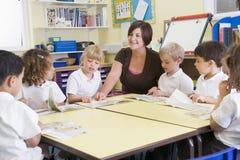 Schoolkinderen en hun leraar in klasse stock fotografie