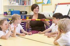 Schoolkinderen en hun leraar in klasse stock afbeeldingen