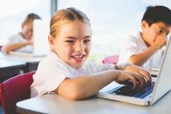 Schoolkinderen gebruikend laptop in klaslokaal stock foto's