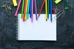 Schoollevering en notitieboekje op een bordachtergrond Vrije ruimte voor tekst royalty-vrije stock afbeeldingen