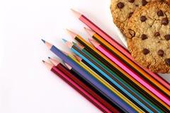 Schoollevering, geïsoleerde potloden en chocoladeschilferkoekjes stock foto's