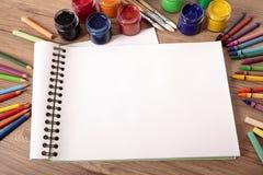 Schoollevering op bureau met leeg kunstboek, exemplaarruimte Stock Fotografie