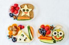 Schoolmaaltijddozen voor jonge geitjes met voedsel in de vorm van grappige gezichten Stock Afbeeldingen