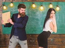 Schoolmaster punishes sexy student with slapping on her buttocks with book. Teacher spanking girl in classroom. Man with stock images