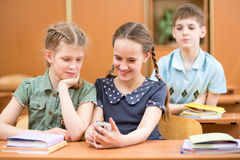 Schoolmates play with mobile phone at lessons pausa Stock Images