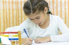 Schoolmeisje bij haar Bureau stock afbeeldingen
