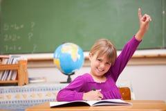 Schoolmeisje dat haar hand opheft om een vraag te stellen royalty-vrije stock foto