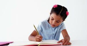Schoolmeisje dat haar thuiswerk doet stock video