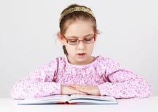 Schoolmeisje dat met glazen boek leest Stock Fotografie