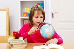 Schoolmeisje dat met meer magnifier zoekt Stock Foto
