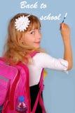Schoolmeisje dat op blauwe achtergrond schrijft Stock Afbeeldingen