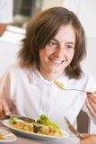 Schoolmeisje dat van haar lunch in school geniet stock afbeelding
