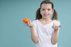 Schoolmeisje dat vruchten en melk toont stock afbeelding