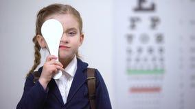 Schoolmeisje die één oog voor volledig visieexamen sluiten, diagnostiek van gezicht stock video