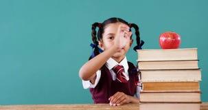 Schoolmeisje die appel op stapel boeken houden stock video