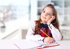 Schoolmeisje die bij bureau binnen achtergrond schrijven Stock Afbeeldingen