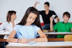 Schoolmeisje die bij Bureau schrijven terwijl Klasgenoten stock afbeeldingen