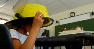 Schoolmeisje die brandbestrijdershelm in klaslokaal dragen op school 4k stock video