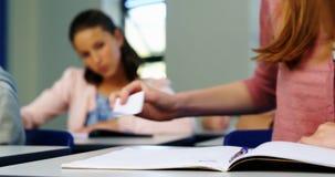 Schoolmeisje die chit tot haar klasgenoot tijdens examen in klaslokaal overgaan stock videobeelden