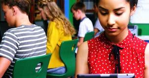Schoolmeisje die digitale tablet gebruiken terwijl andere studenten die op computer in klaslokaal bestuderen stock videobeelden